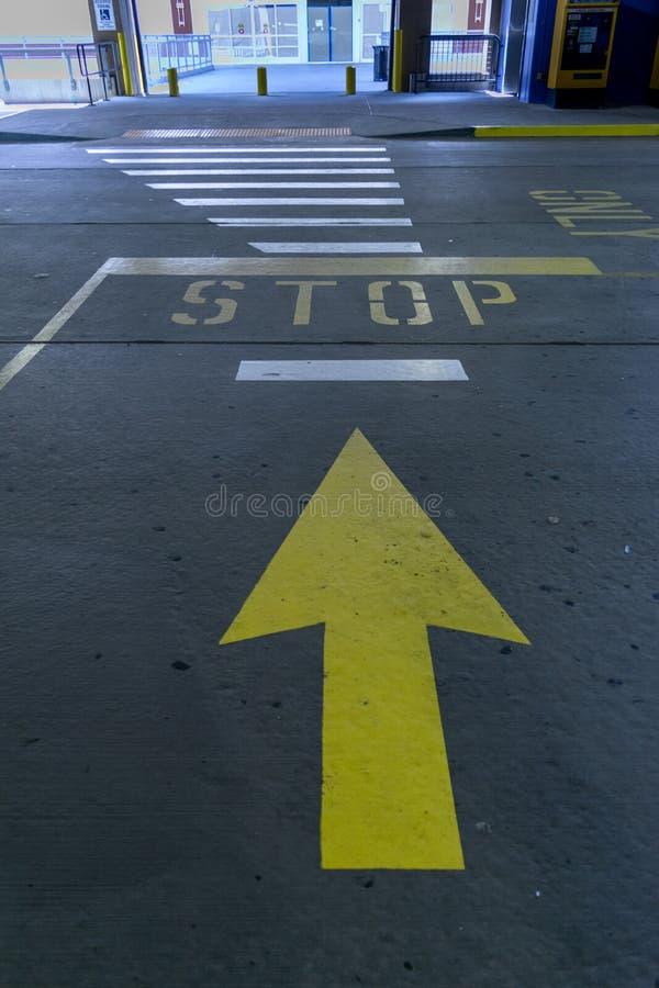 一条指向停车牌的大黄色箭头街道标号 库存图片