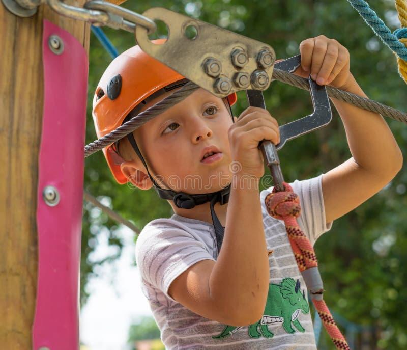 一条攀岩运动员领带每在绳索的结 人为上升做准备 孩子学会栓结 检查保险 免版税库存照片