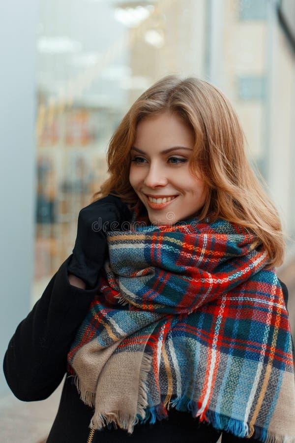 一条时兴的温暖的羊毛围巾的快乐的愉快的年轻女人在黑手套的一时髦的黑色大衣站立并且微笑着 免版税库存图片