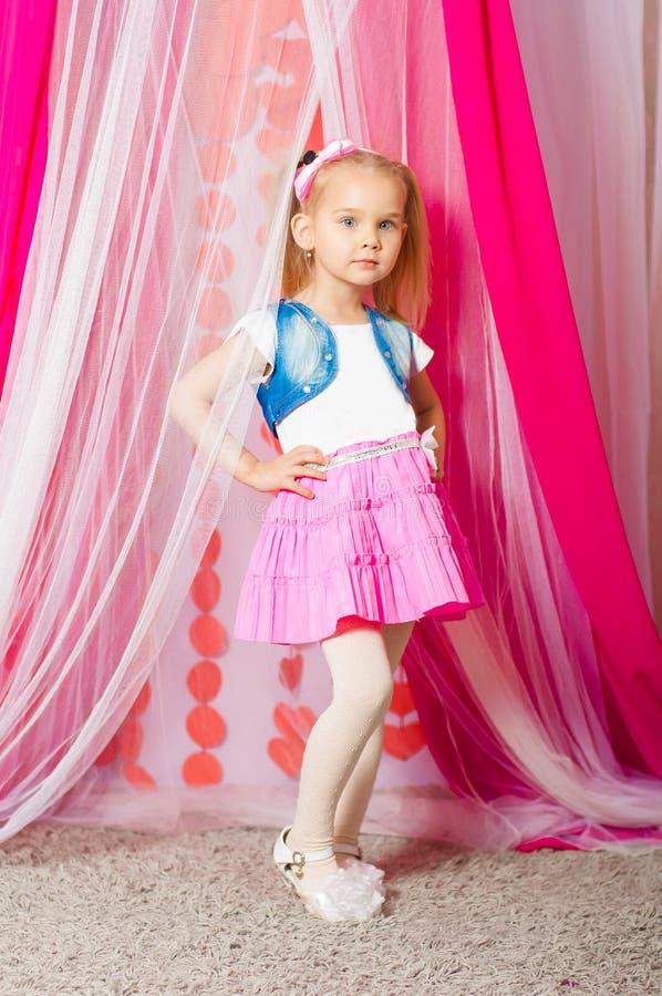 一条桃红色裙子的小女孩 库存图片