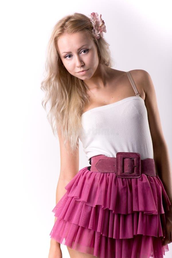 一条桃红色裙子的白肤金发的女孩 免版税库存照片