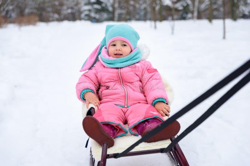 一条桃红色连衫裤的女孩在一个多雪的冬天公园走 免版税图库摄影