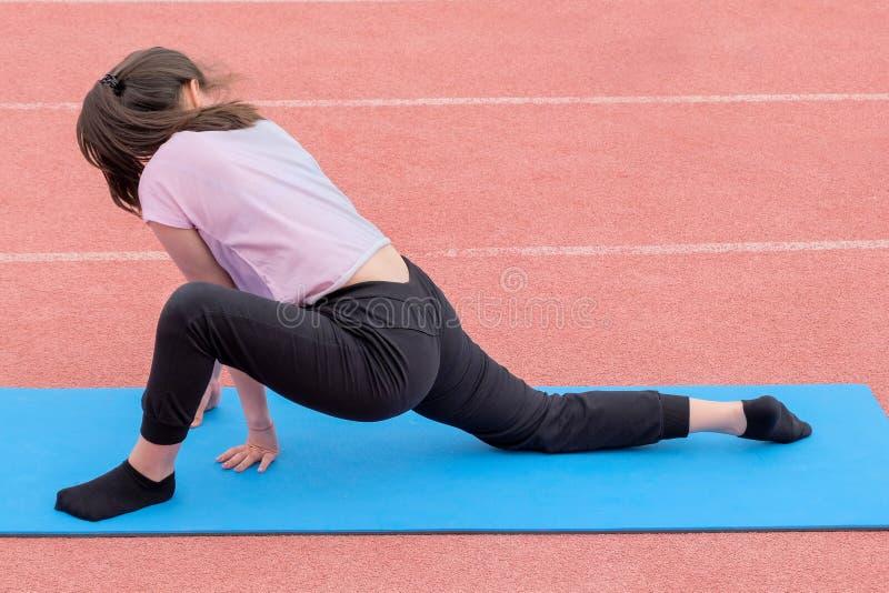 一条桃红色T恤杉和黑裤子的一个女孩露天执行健身锻炼 回到视图 舒展训练 免版税库存图片