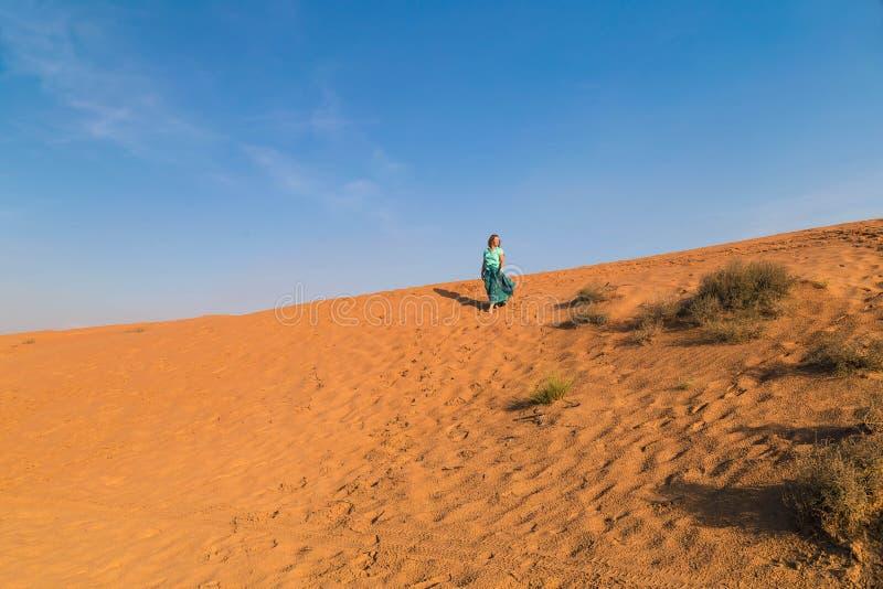 一条泥泞的绿松石裙子的妇女有装饰品和一件单音绿松石衬衣的一在橙色沙丘顶部在沙漠 图库摄影
