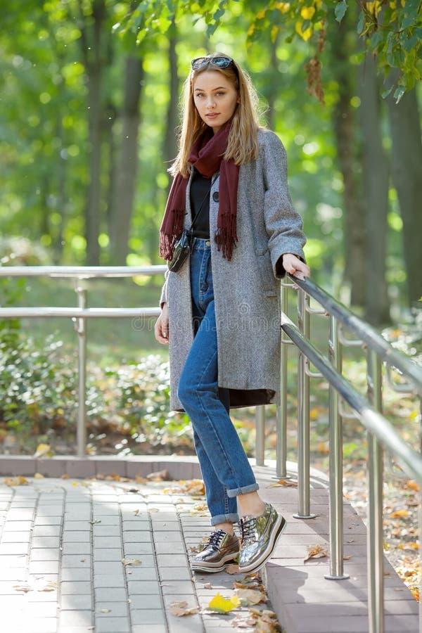 一条温暖的围巾蓝色牛仔裤时髦鞋子和舒适外套的美丽的时髦的少妇走在秋天城市公园的 库存照片