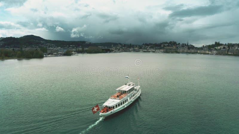 一条游览小船的空中射击有挥动的移动在琉森湖,瑞士的瑞士旗子 免版税图库摄影