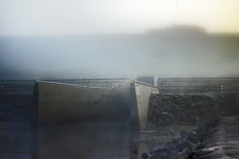 一条溢洪道的朦胧的早晨视图从一个大水库的 免版税库存照片