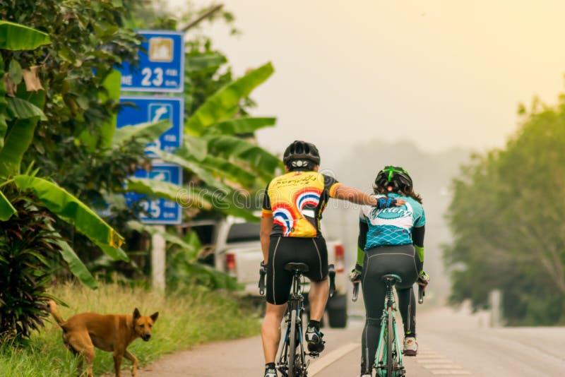 一条漫长的路的年轻骑自行车者 免版税库存照片