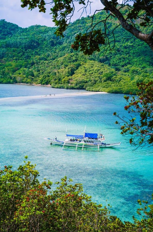 一条热带海岛蛇的美丽的景色与白色传统banca小船充分的游人的 El Nido,巴拉望岛,菲律宾 免版税库存照片
