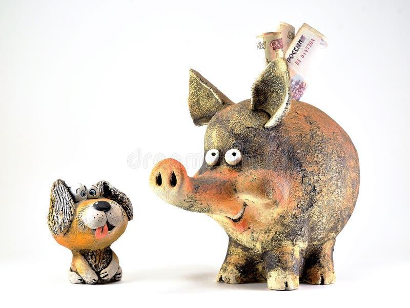 一条狗的黏土小雕象与非常突出他的舌头和存钱罐的 免版税库存照片