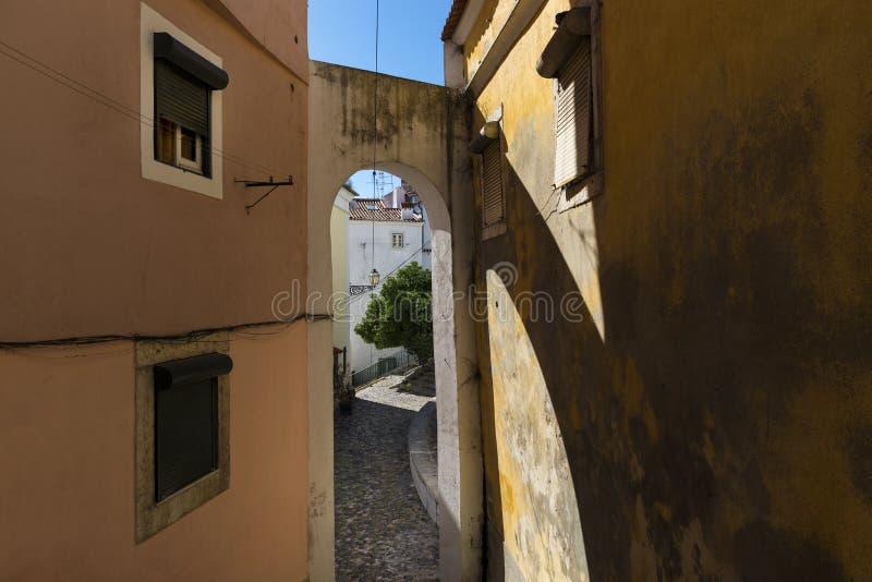 一条狭窄的街道和传统老大厦的看法有曲拱的在Alfama历史的邻里在里斯本,葡萄牙 库存照片