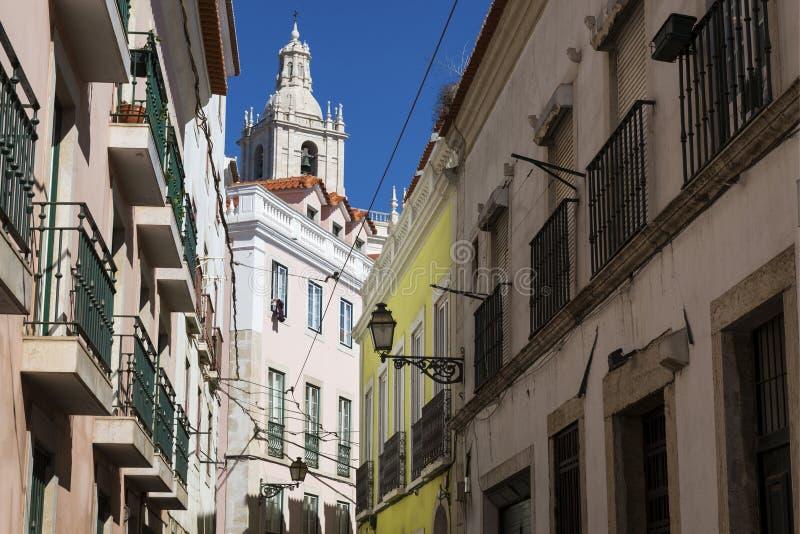 一条狭窄的街道和大厦的看法与圣地Vincente de Fora教会的塔backrgound的,在历史的邻居 免版税库存照片