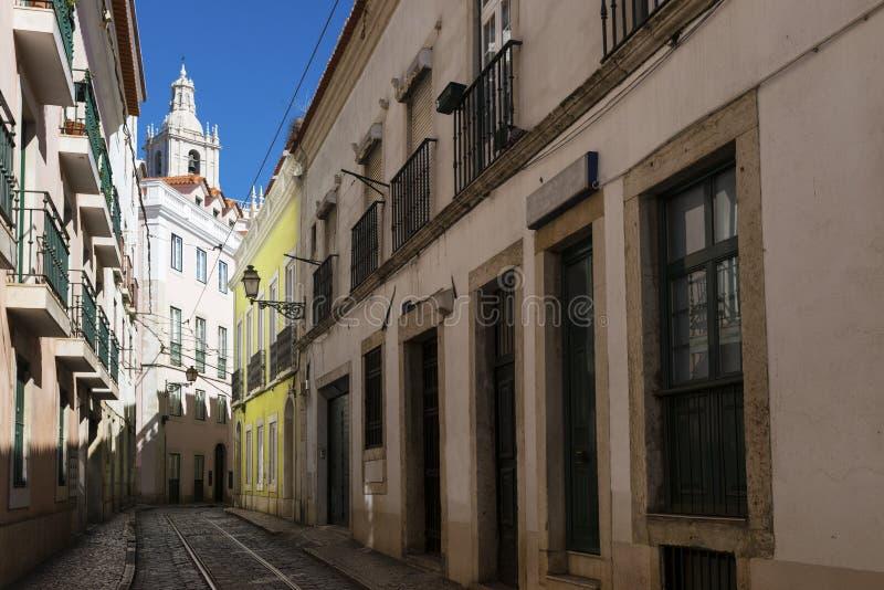 一条狭窄的街道和大厦的看法与圣地Vincente de Fora教会的塔backrgound的,在历史的neighborh 免版税库存照片
