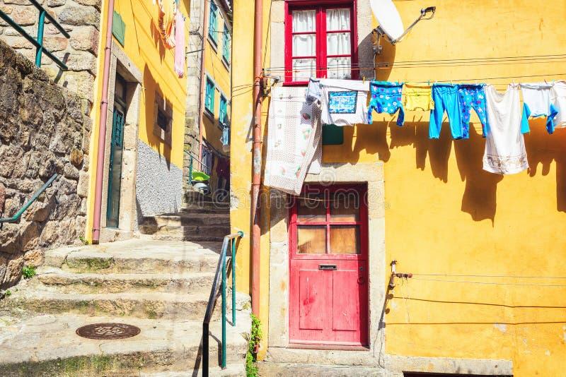 一条狭窄的街道的五颜六色的房子有垂悬的洗衣店的, Ribeira区,波尔图,葡萄牙 库存照片