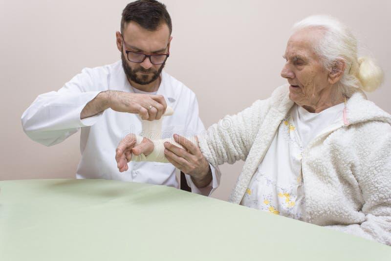 一条白色围裙的医务人员在一名非常老灰色妇女的腕子上把路轨和选矿放在一件白色晨衣 免版税图库摄影
