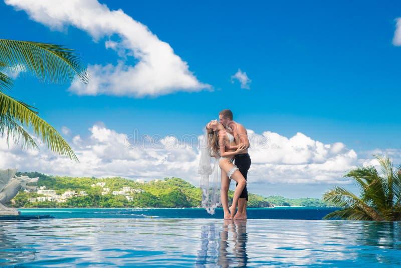 一条白色比基尼泳装、面纱和袜带的美丽的年轻新娘在她 免版税图库摄影