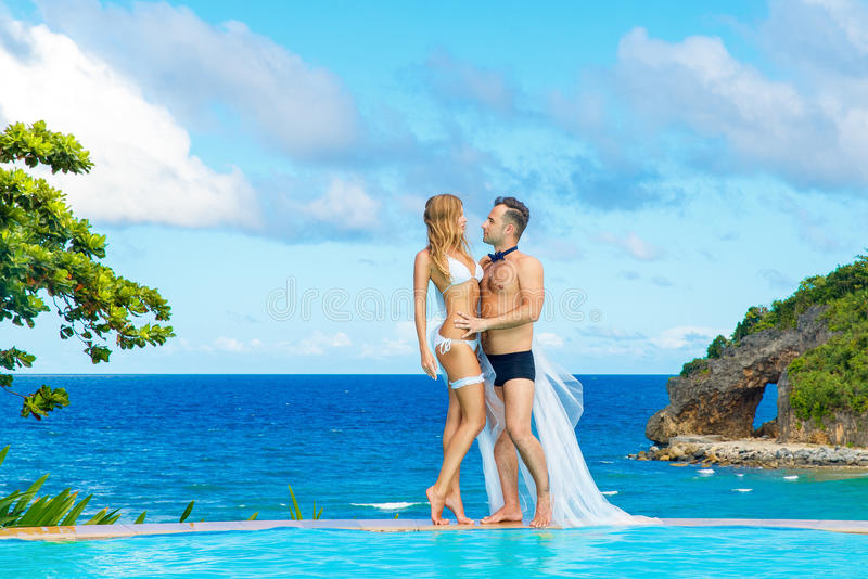 一条白色比基尼泳装、面纱和袜带的美丽的年轻新娘在她 库存图片