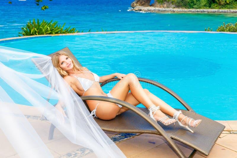 一条白色比基尼泳装、面纱和袜带的美丽的年轻新娘在她 库存照片