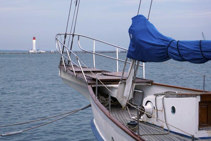一条白色航行游艇的弓反对蓝色海的有在弓的船锚的 灯塔在后部 图库摄影