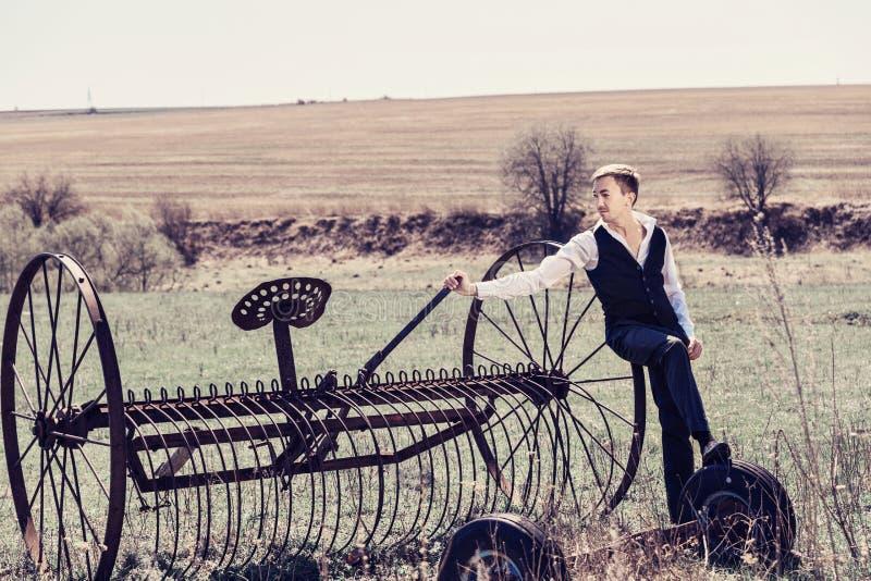 一条白色衬衣和蓝色裤子的一个年轻人倾斜了反对干草堆 免版税库存图片