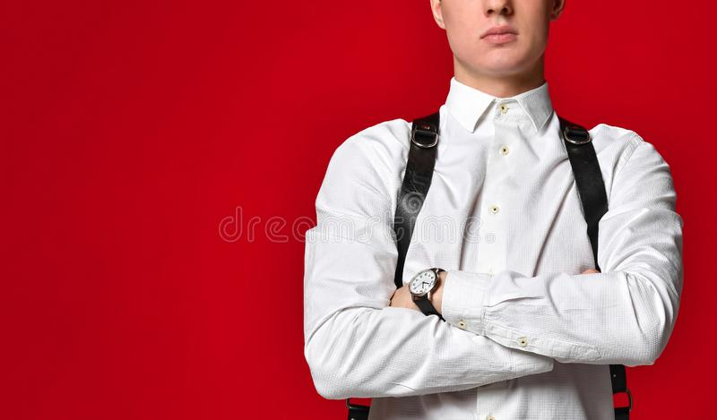 一条白色衬衫和传送带的时髦的骄傲的年轻人在红色背景 在一个闭合的姿势的手 免版税库存照片