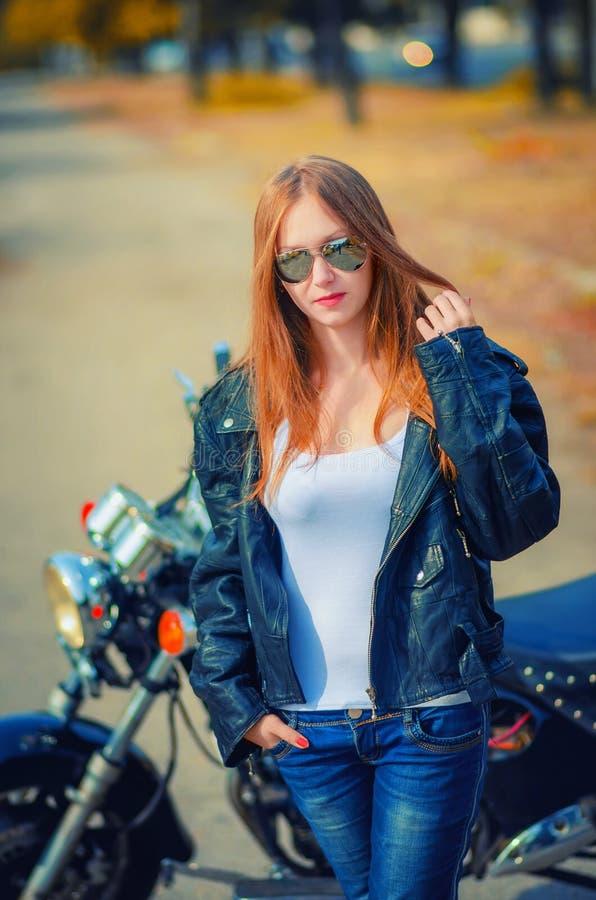 一条皮夹克、白色衬衣和蓝色牛仔裤的妇女在glas 免版税库存照片