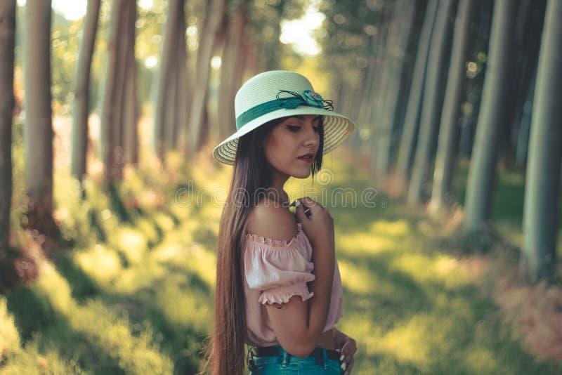一条相当长发深色的西班牙女孩佩带的白色太阳帽子桃红色女衬衫和短的蓝色牛仔裤的画象 库存照片