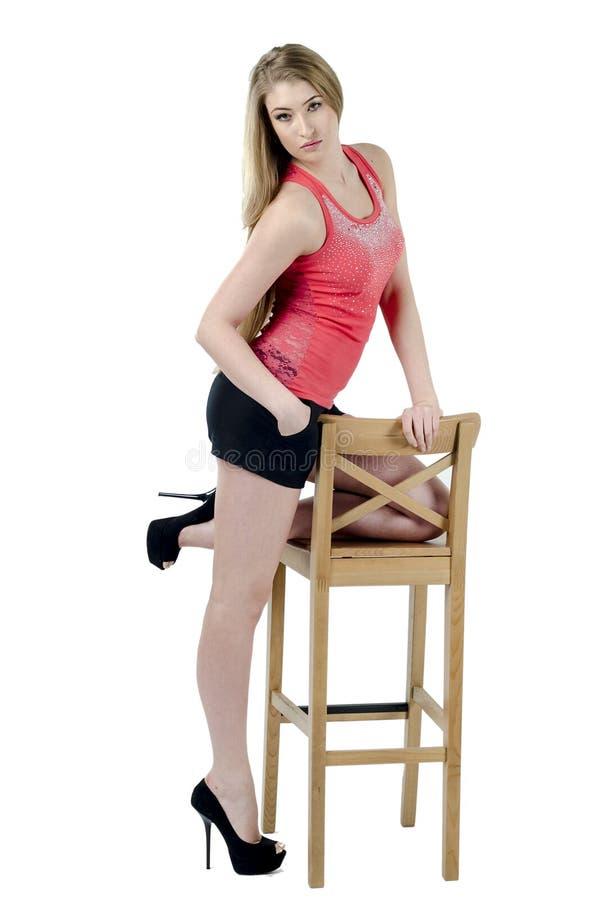 一条短裙的美丽的长发快乐的女孩坐椅子和打手势 免版税库存照片