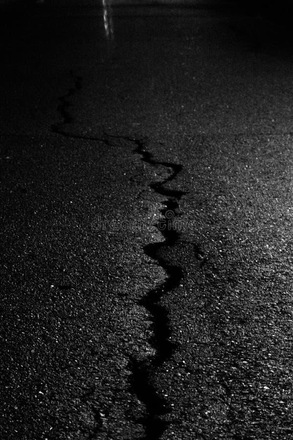 一条破裂的边路的摘要在晚上 库存照片