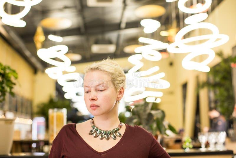 一条红色礼服和项链的年轻金发碧眼的女人从大汤匙在她的脖子上 免版税库存照片