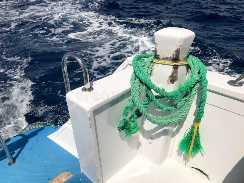 一条绿色强的耐久的重织品船绳索,停泊处的,中止一条绳索附加一艘浮动船,反对蓝色s的一条小船 库存图片
