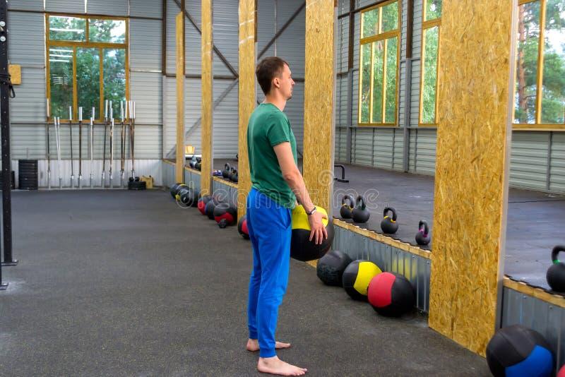 一条绿色T恤杉和蓝色裤子的人在健身房,投掷训练 免版税库存照片