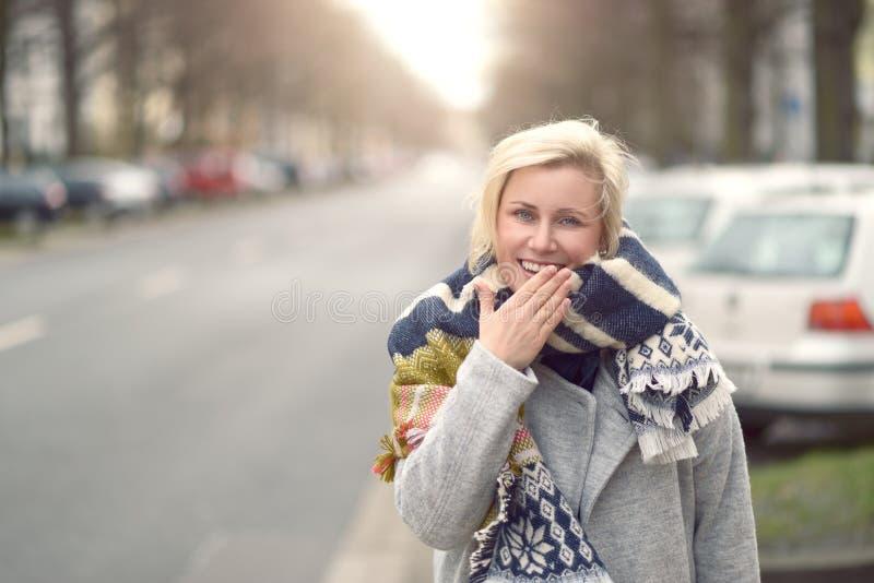 一条羊毛制围巾的微笑的可爱的少妇 库存照片