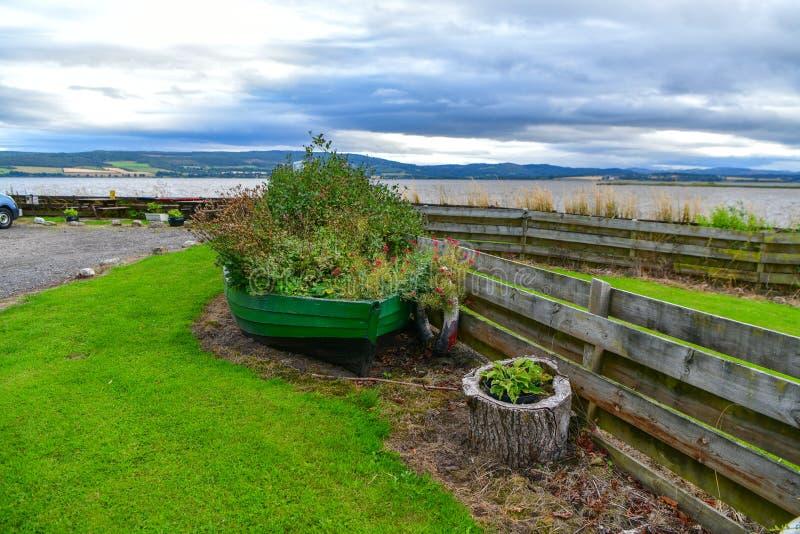 一条老小船在背景中把一个花圃一个美丽的湖苏格兰变成 库存照片