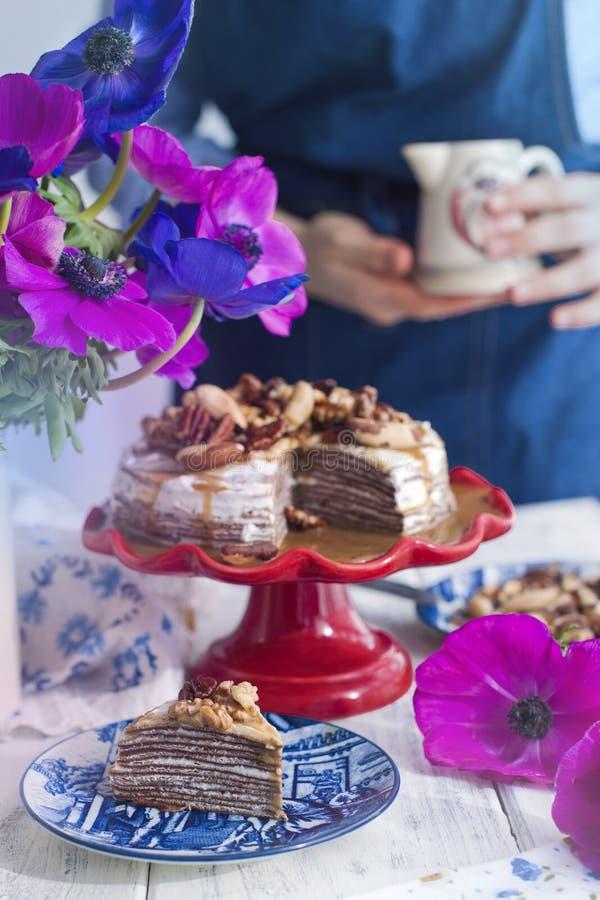 一条蓝色围裙在厨房里和蛋糕的,在花瓶的花一个女孩 古色古香的企业咖啡合同杯子塑造了新鲜的早晨好老笔场面打字机 免版税库存照片