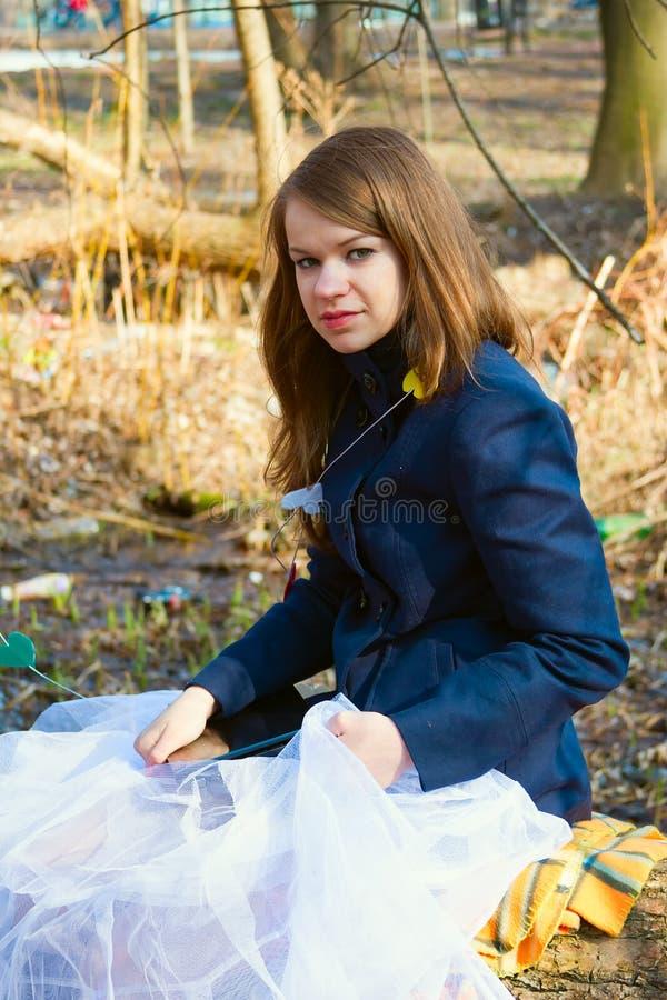 一条蓝色外套和白色薄纱裙子的女孩 免版税库存照片