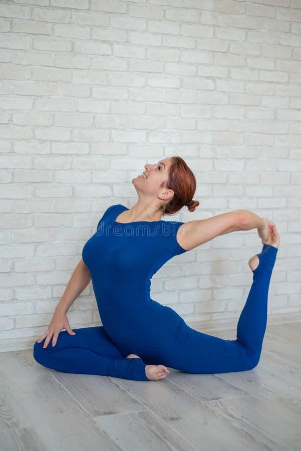 一条蓝色连衫裤的红发妇女在一间明亮的屋子实践瑜伽 女孩在鸽子,弯的姿势松劲  图库摄影