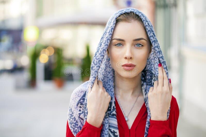 一条蓝色围巾的美丽的少妇在夏天街道城市 免版税库存照片