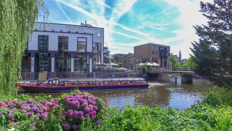 一条蓝色Boat Company游览小船在夏天采取在一条运河下的人在阿姆斯特丹 库存图片