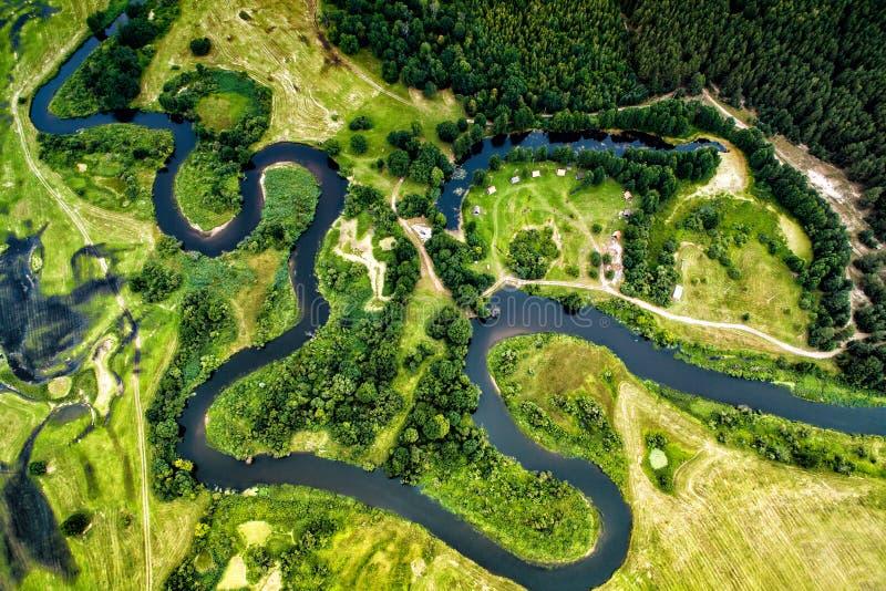 一条蜿蜒的河的谷的顶视图在绿色领域中的 库存照片