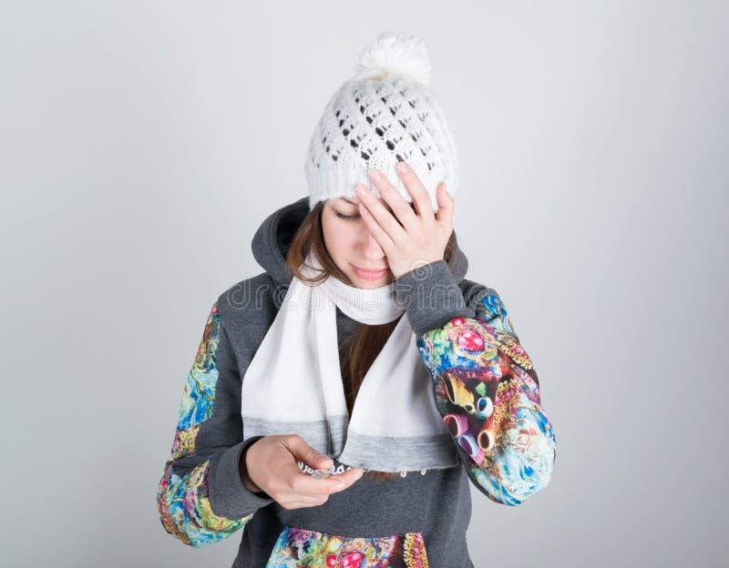 一条被编织的帽子和围巾的少妇,握在温度计的手 她似乎病残,拿着他的头 免版税库存照片
