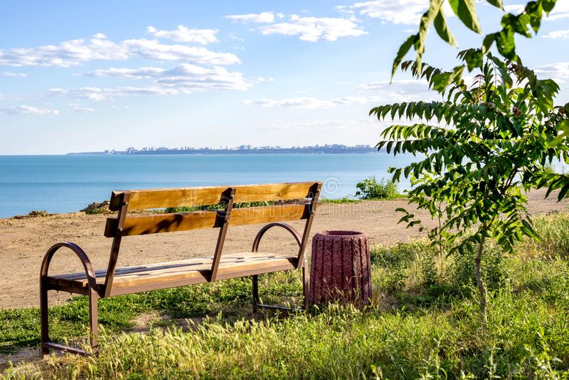 一条长凳的一种简单的minimalistic布局在看往海洋海海滩的绿草的浇灌与蓝色空白的空的copyspa 免版税库存照片