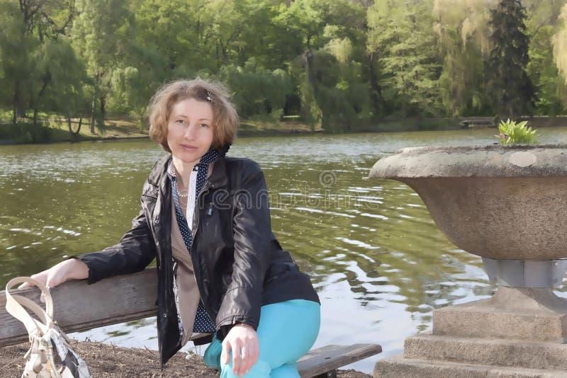 一条长凳的年轻可爱的女孩由湖 免版税库存图片