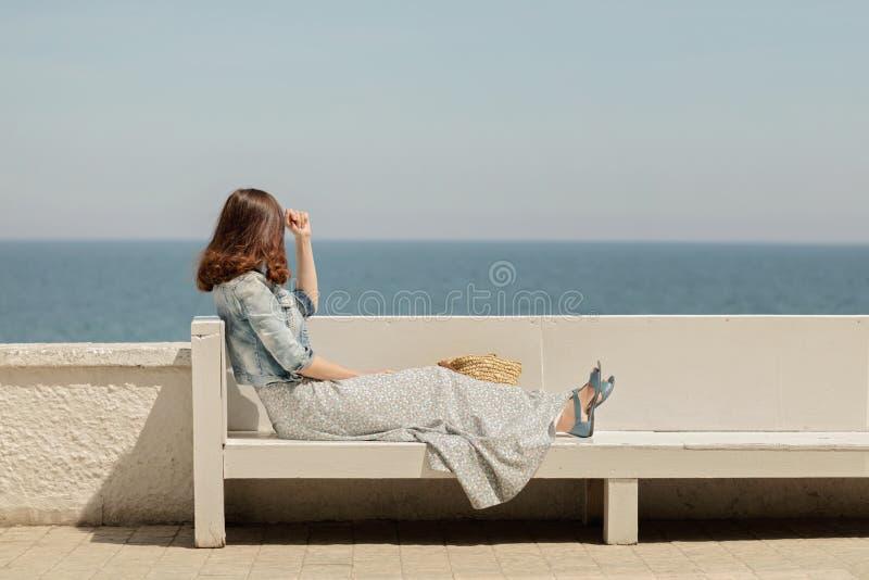 一条长的裙子的年轻美丽的妇女坐在backg的一条长凳 免版税库存图片