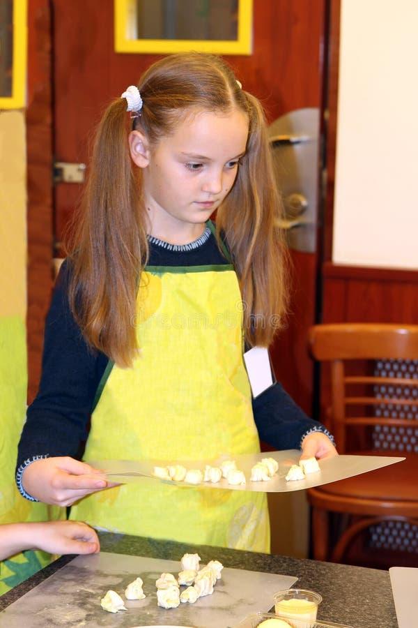 一条黄色围裙的一女孩拿着有面团片的一块砧板 免版税库存照片