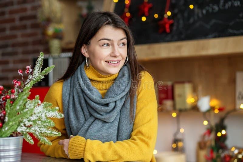 一条黄色被编织的毛线衣和围巾的年轻微笑的妇女 概念家,舒适,生活方式,秋天,冬天,咖啡馆 免版税库存照片