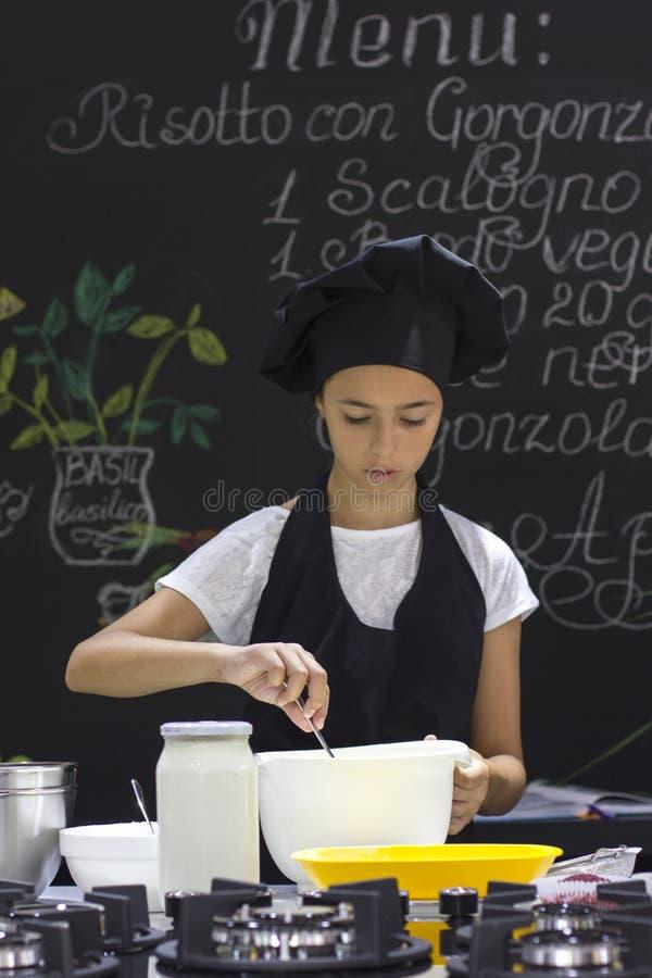 一条黑围裙和厨师` s帽子的俏丽的女孩厨师搅动与sp 免版税库存图片