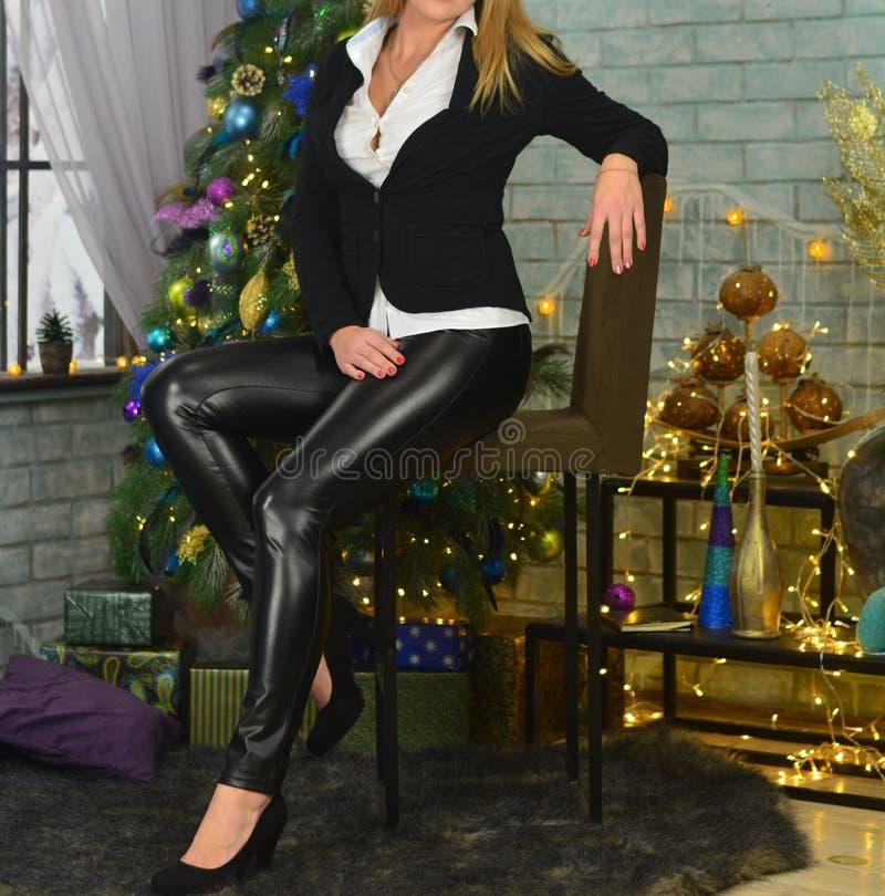 一条黑夹克、白色衬衣和黑亮漆裤子的一个女孩坐在圣诞树和beautifu的背景的一把椅子 免版税库存图片