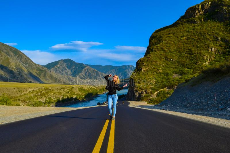 一条黑柏油路有黄色标号的和沙子的女孩金发碧眼的女人在路旁 库存图片