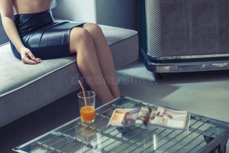 一条黑裙子的一个女孩坐沙发在与一杯的一张桌附近汁液和杂志 免版税库存照片